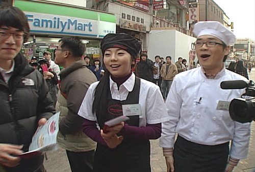 So Hee Distributing Flyers on the Streets